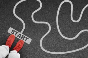 Roter Schuh auf asphaltierter Startmarkierung mit weißer Linie