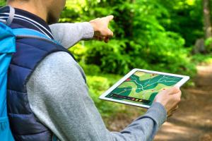 Mann wandert mit Tablet und GPS-Gerät